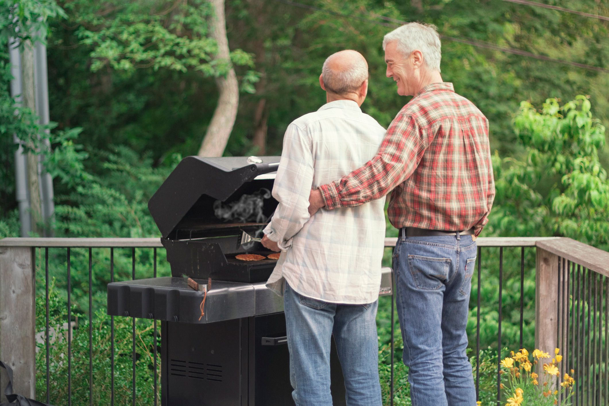 Senior mature older gay male couple grilling food together on outdoor grill, while one has his arm around the other and they look affectionately at each other