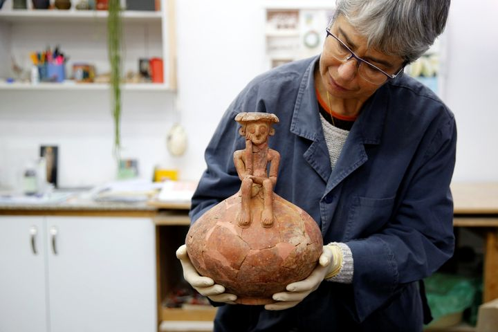 Conservationist Elisheva Kamaisky, shows journalists a 3,800 year-old pottery jug with a rare statuette, discovered during ex