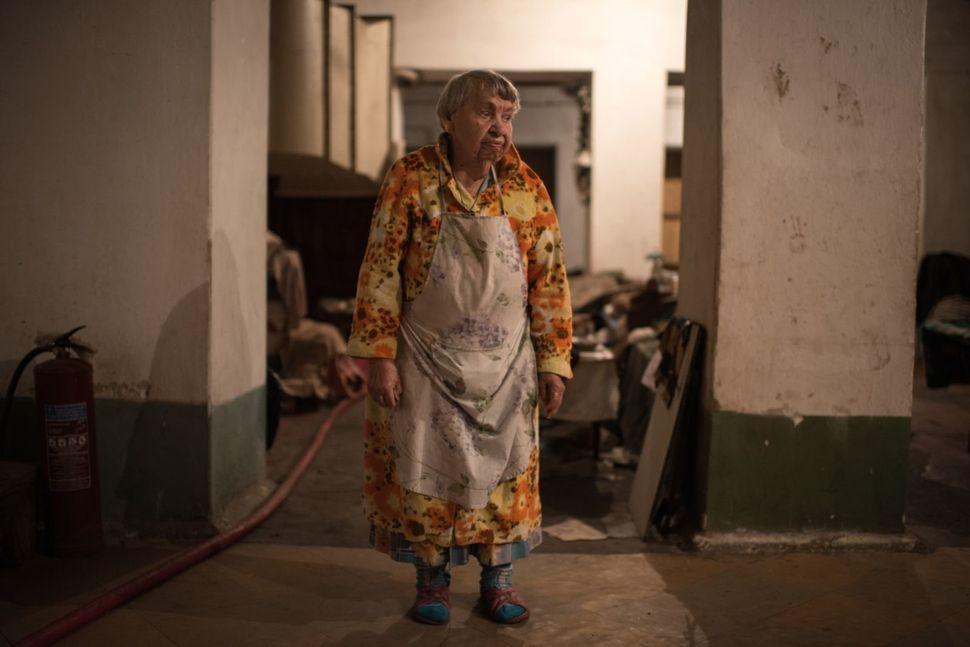 Mariya Tkachenko, 85, prepares and eats her meal in the bunker's kitchen area.