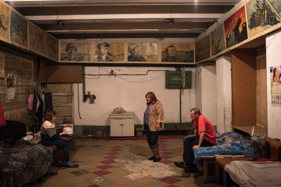 Valentina Maronova, center, stands in the main common area inside the bunker. She is concerned about the looming winter seaso