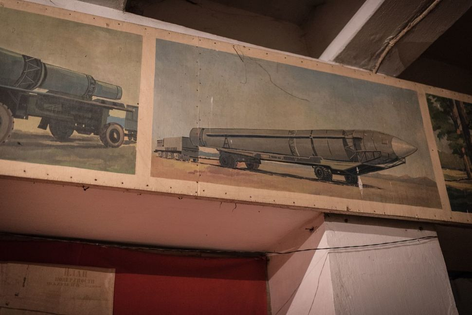 Soviet-era paintings and slogans adorn the walls above makeshift beds and shelves that people have set up over the last two y