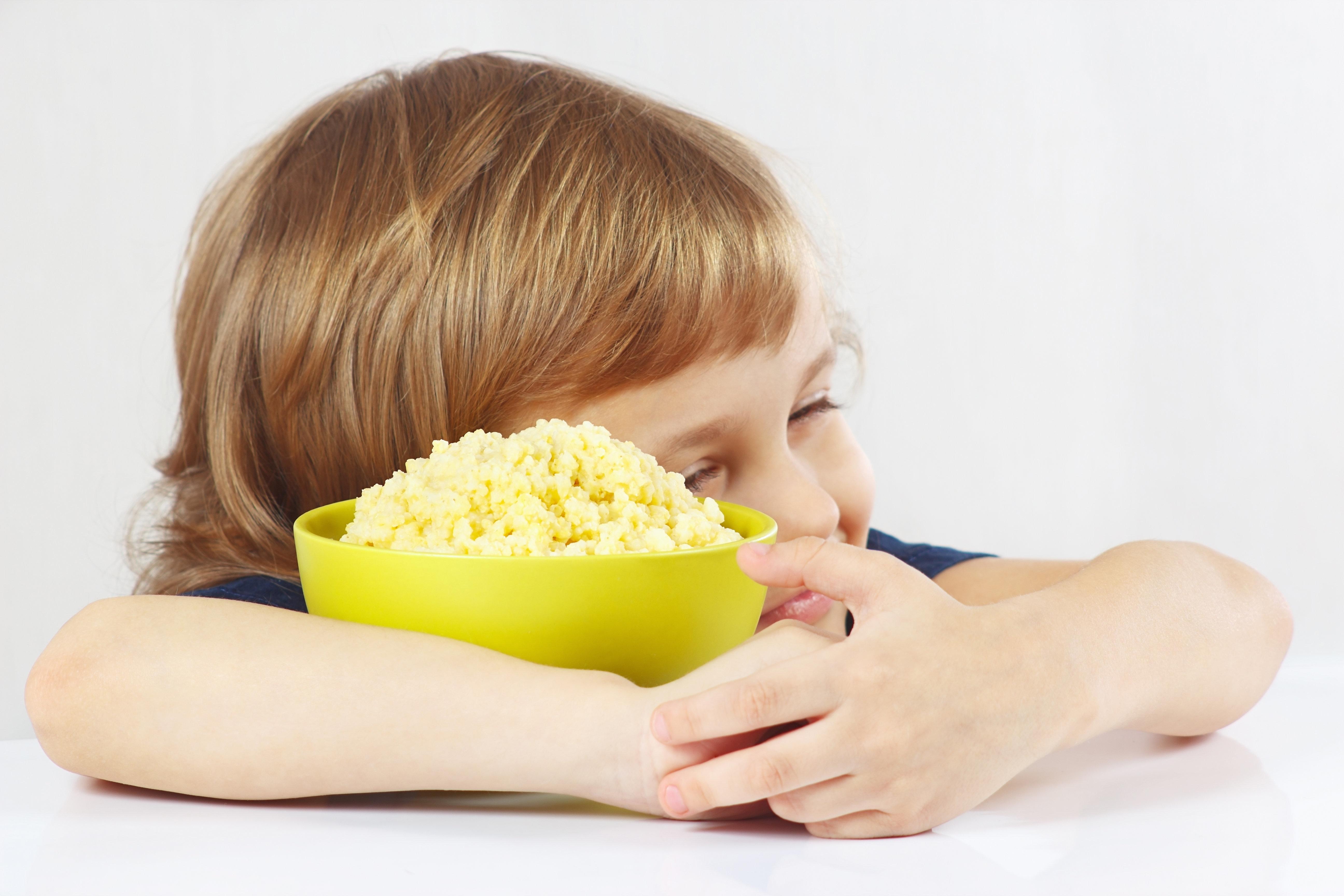 Beautiful child hugging a bowl of millet porridge favorite on white background