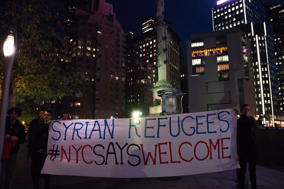 Demonstrators hold upsigns of support for refugees at arally last year against Donald Trump's proposed ban on asy