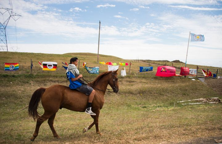 A youth rides a horse over a fenced area of land set aside for the Dakota Access Pipeline in North Dakota.