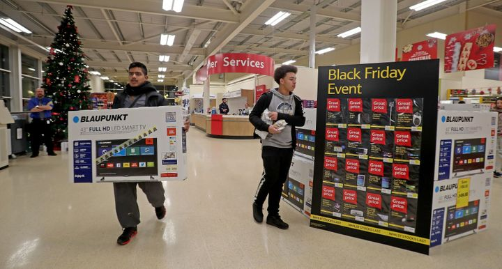 A shopper is pictured carrying a TV set out of a Tesco Extra store in Manchester. Notice the lack of crowds.