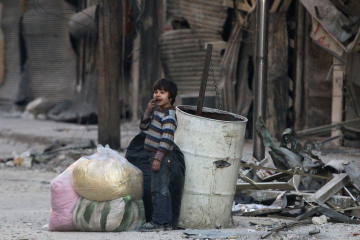 A boy stands in the damage of Aleppo's besieged al-Shaar neighborhood.