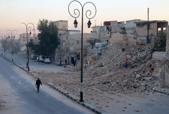A man walks past a damaged site in Aleppo'sQadi Askar neighborhood.