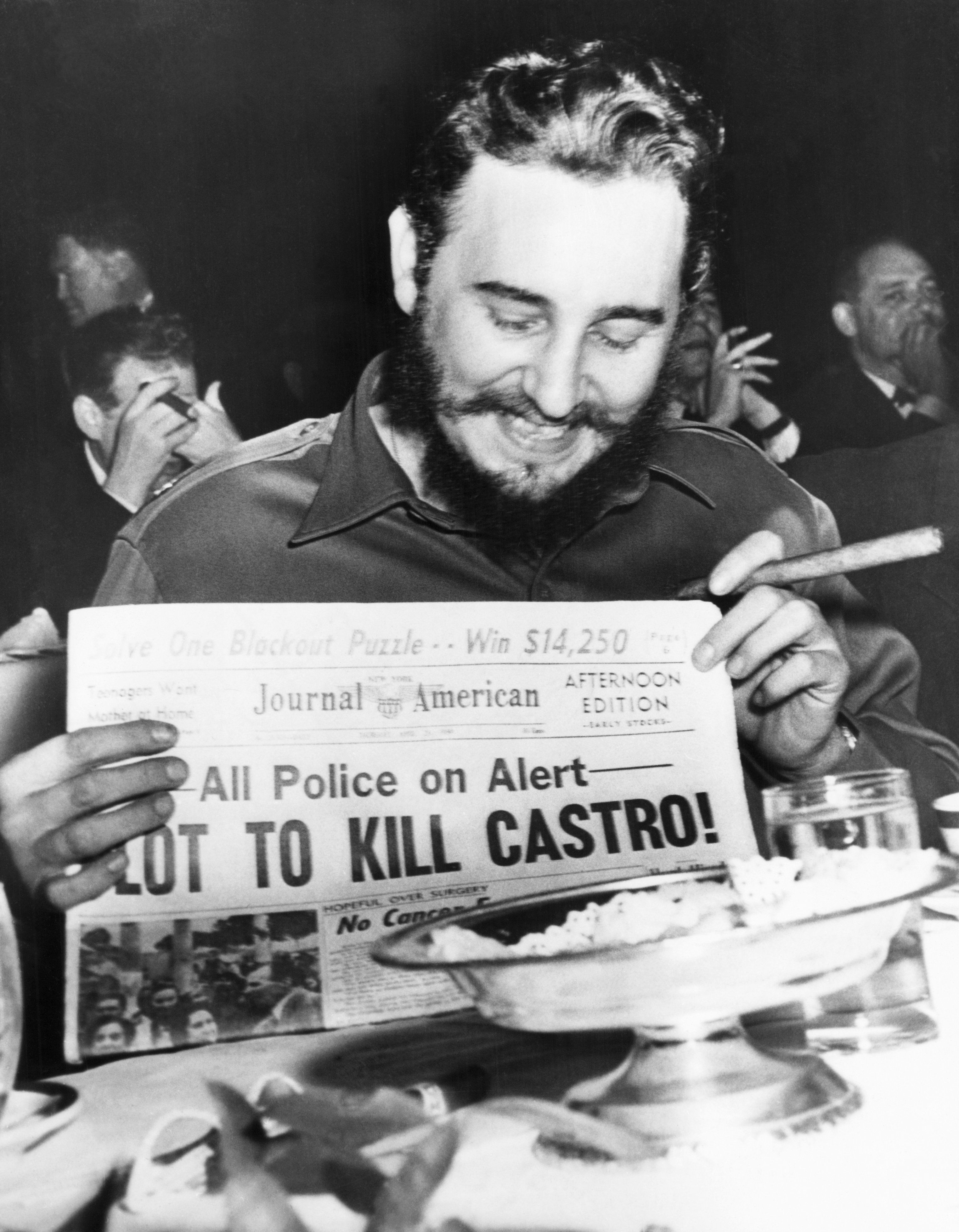 Seeming quite amused, Castro holds up a newspaper headlining the discovery of a plot to kill him in New York City on April 23
