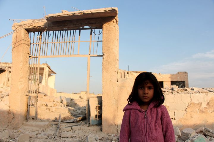 A Syrian girl is seen in front of the school in Haas that was destroyed by an Oct. 26 airstrike.