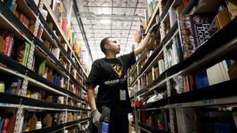 A worker gathers items for delivery from the warehouse floor at Amazon's distribution center in Phoenix, Arizona November 22, 2013. The web-based retailer is preparing for Cyber Monday, which is traditionally the busiest day of the year for online purchases, and falls on December 2 in 2013. REUTERS/Ralph D. Freso   (UNITED STATES - Tags: BUSINESS EMPLOYMENT)