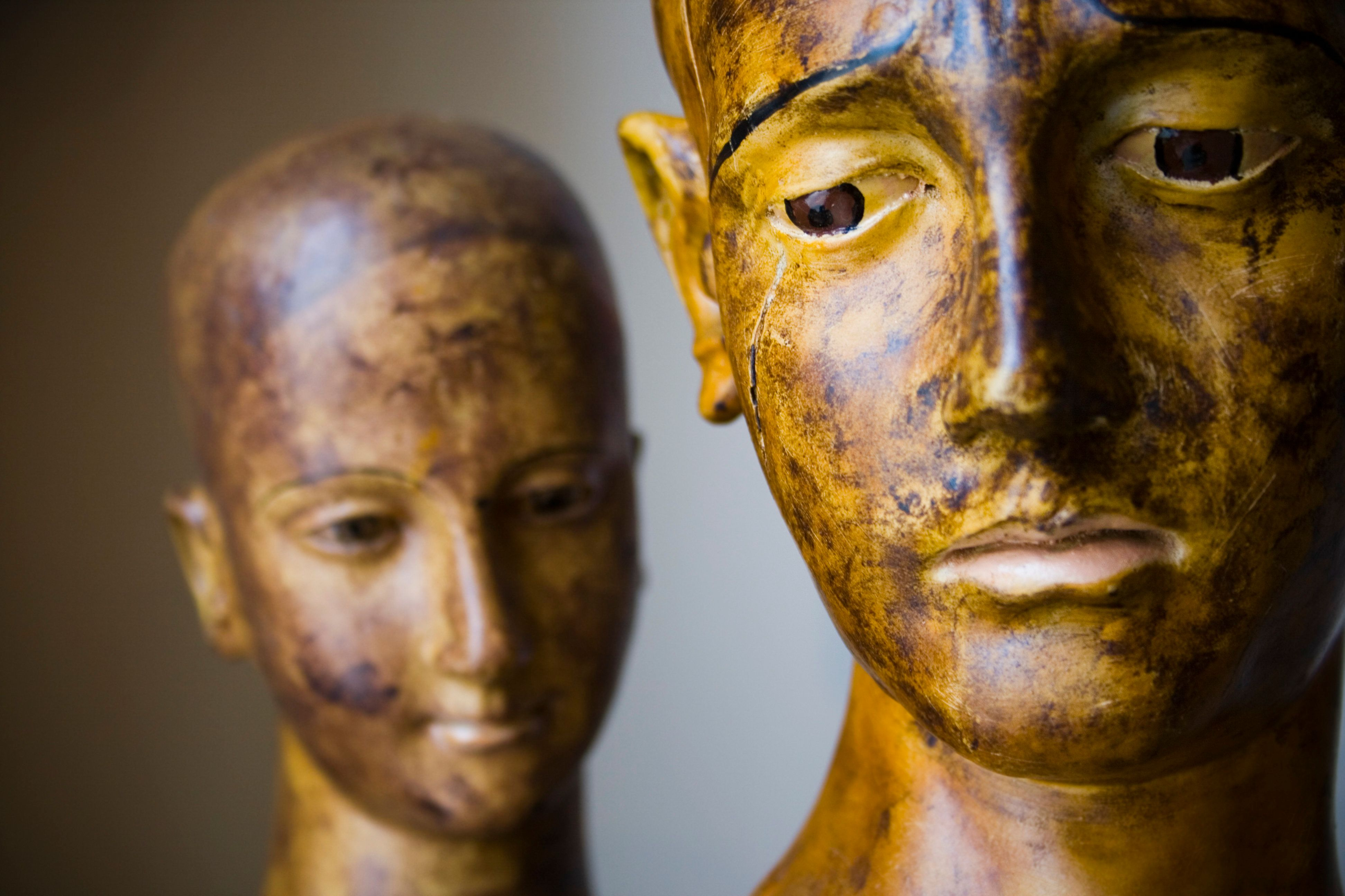 Closeup of a pair of old dirty carved wooden saint heads.