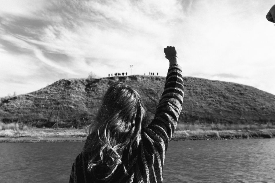 A protester stands in defiance as militarized police patrol a sacred burial ground, far from the DAPL work site.