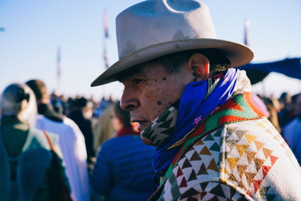 An Elder looks on during the morning prayers and announcements that start each day at the Oceti Sakowin, the largest camp at