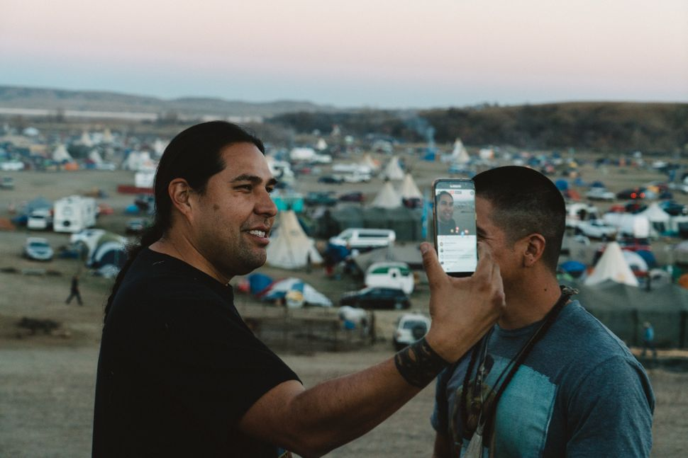 """Dallas Goldtooth of the Indigenous Environmental Network hosts a livestream from """"Facebook hill,"""" one of the only places in O"""