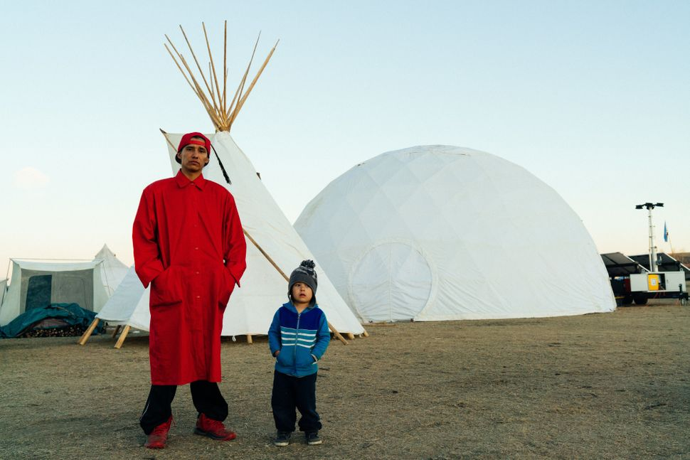 """Two protestersstandin front of a geodesic dome brought by the Burning Man group """"Red Lightning."""""""