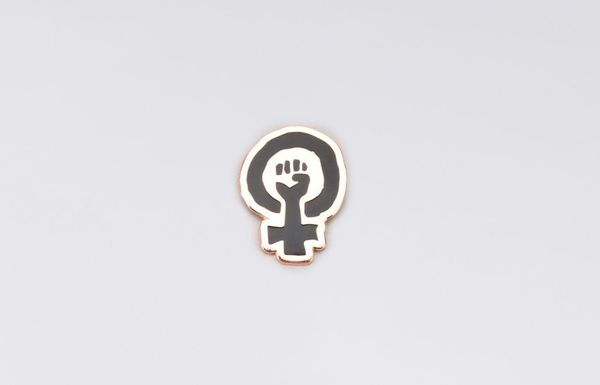 """$10, Wildfang. <a href=""""http://www.wildfang.com/feminist-fist-pin115393.html"""" target=""""_blank"""">Buy here</a>."""
