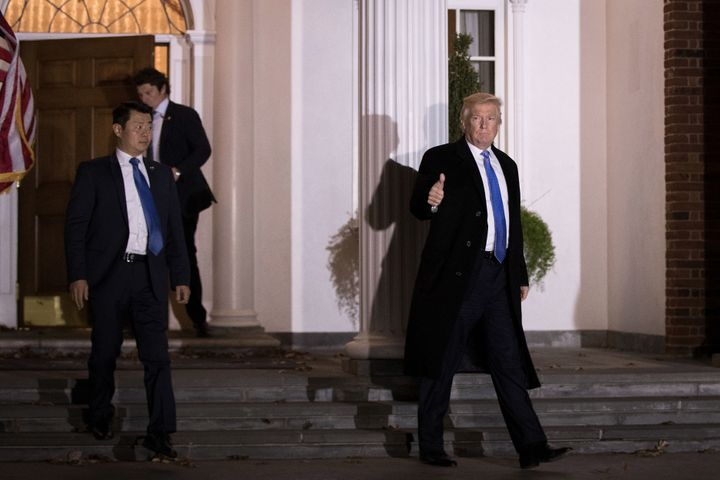 Trailed by U.S. Secret Service agents, President-elect Donald Trump leaves the clubhouse following a full day of meetings at