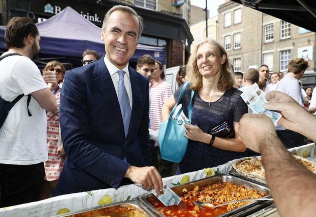 Bank of England Governor Mark Carney demonstrates the new £5 note's