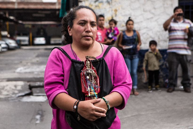 Devotee who brought her Lady in Red to be blessed at the Santa Muerte shrine in Tepito
