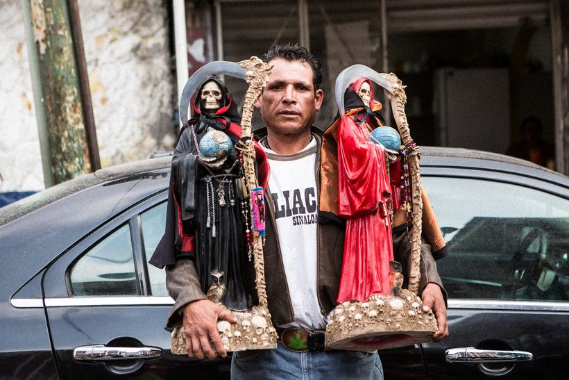 Devotee at Tepito shrine with his Santa Muertes of protection and passion