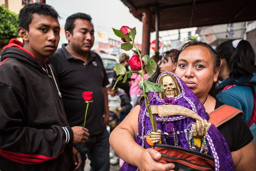 A devotee at the Tepito shrine with her purple Santa Muerte for healing