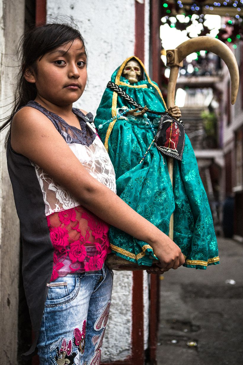 A young devotee at the Tepito shrine with her handcrafted Santa Muerte