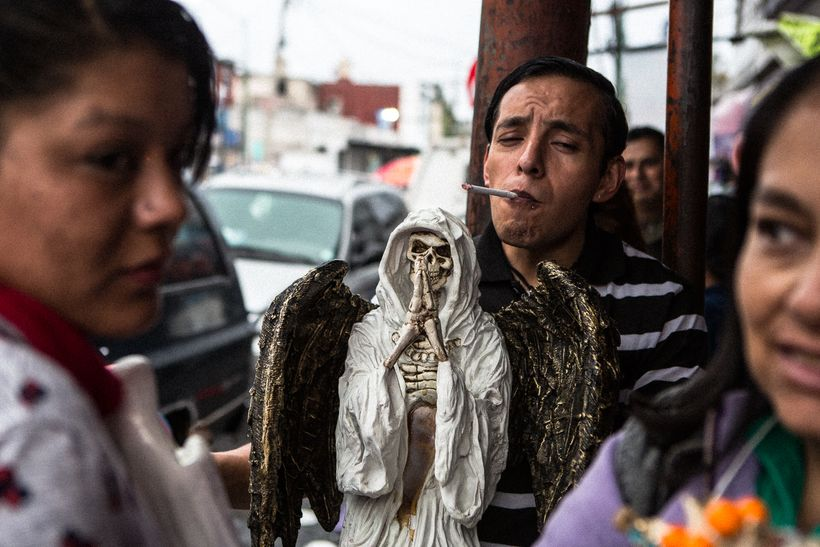 A devotee with his Angel of Death at the Santa Muerte shrine in Tepito