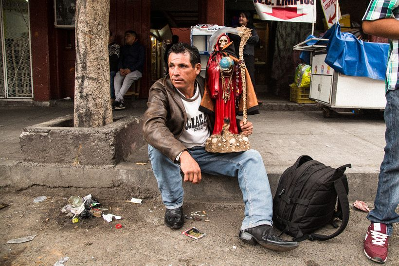 A devotee at the Santa Muerte shrine in Tepito with his Lady in Red for love and passion