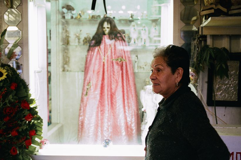 Santa Muerte Godmother Enriqueta Romero with the most famous effigy of the Bony Lady at her Tepito shrine