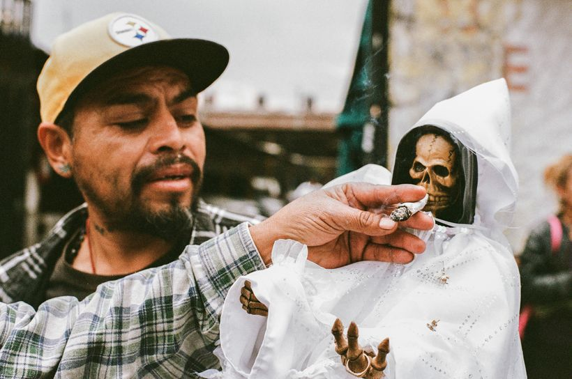 A devotee offering a marihuana joint to the Bony Lady at the Santa Muerte shrine in Tepito