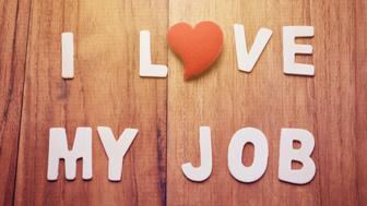 Alphabet letter with heart shape make text, I Love My Job, on wood table. Business concept in I love my job motivation, retro filter, vintage tone, and glow light effect.