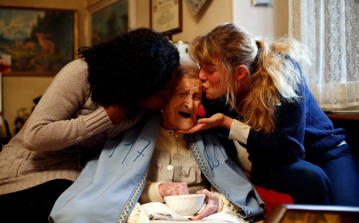 Emma Morano receives kisses from her caregivers, Malgorzat Ceglinska and Yamilec Vergara, during her 117th birthday part
