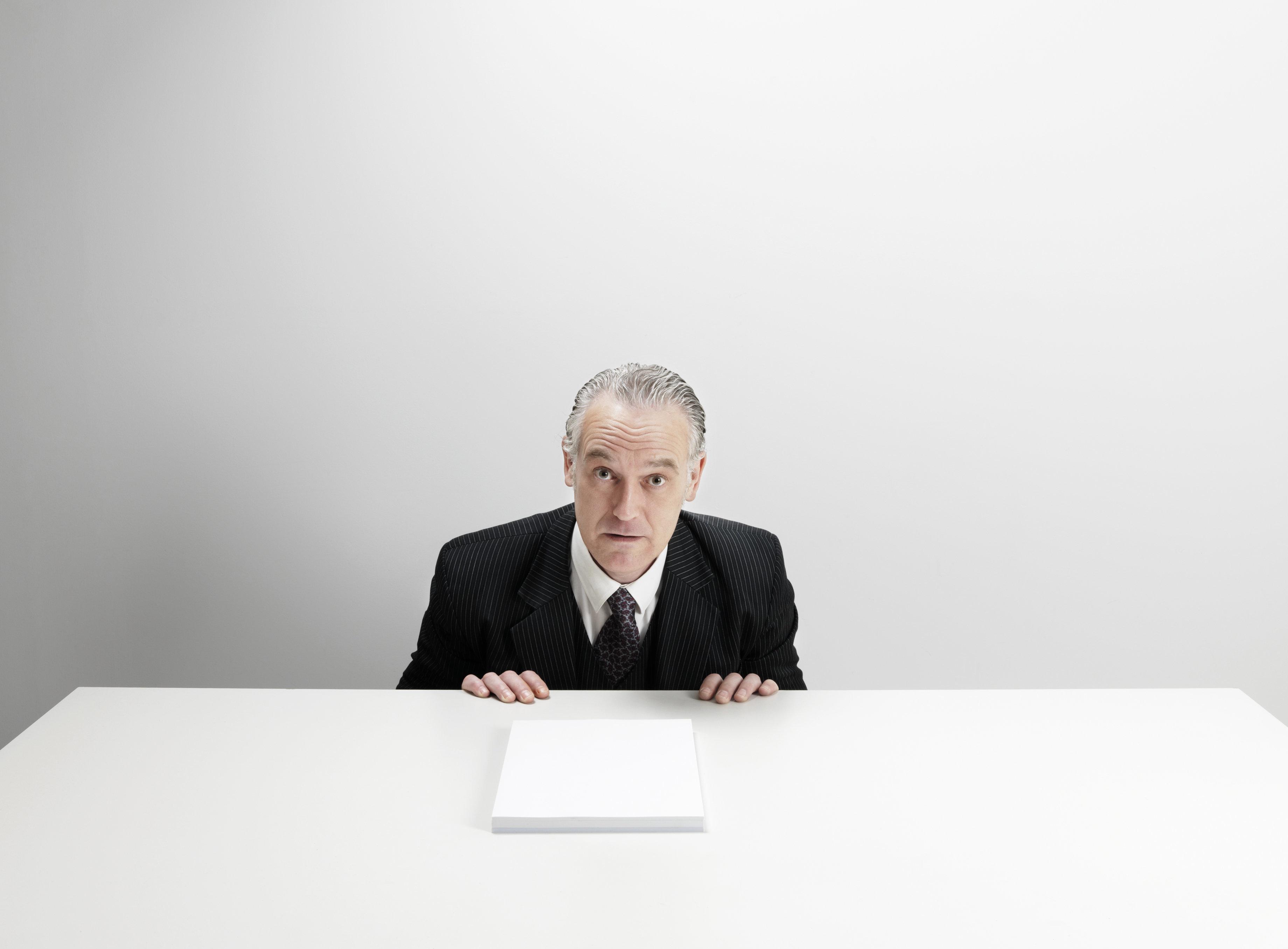 man in suit behind desk looking surprised,49-50 years,studio shot,white paper,Business