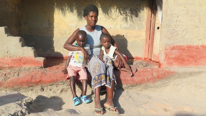 <p>Mother with her children in front of her home in Zambia</p>