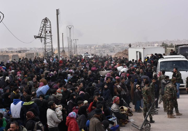 Syrians that evacuated the eastern districts of Aleppo gather to board buses, in a government held area in Aleppo, Syria in t