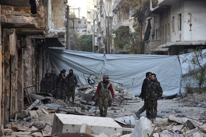 Syrian government soldiers walk amid rubble of damaged buildings, near a cloth used as a cover from snipers, after they took