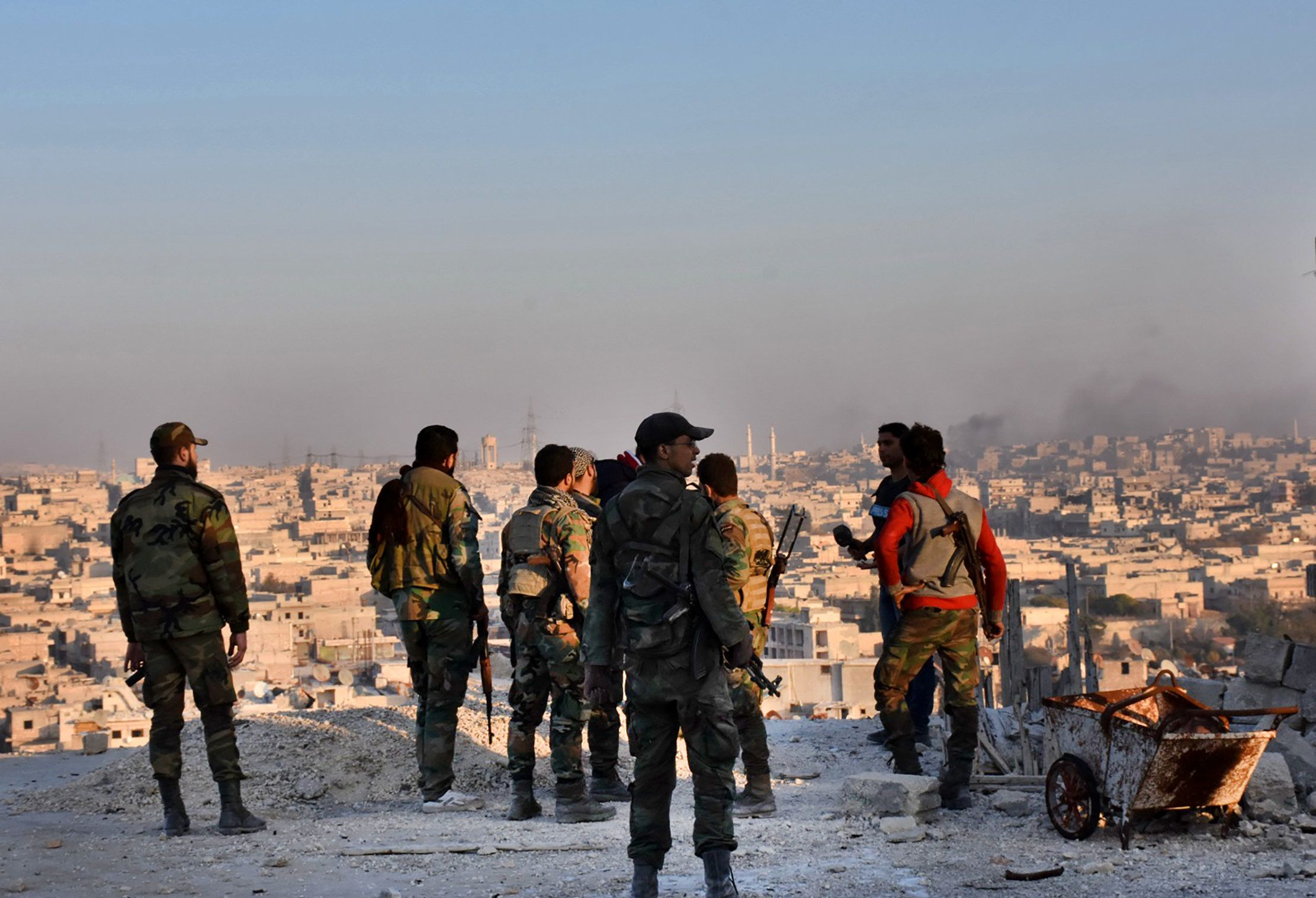 Syrian pro-government forces stand on top of a building overlooking Aleppo in the city's Bustan al-Basha neighbourhood on November 28, 2016, during their assault to retake the entire northern city from rebel fighters.   In a major breakthrough in the push to retake the whole city, regime forces captured six rebel-held districts of eastern Aleppo over the weekend, including Masaken Hanano, the biggest of those in eastern Aleppo.    / AFP / GEORGE OURFALIAN        (Photo credit should read GEORGE OURFALIAN/AFP/Getty Images)