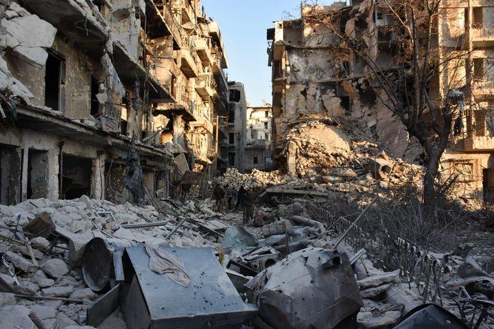 Syrian pro-government forces walk amidst heavy destruction in Aleppo's Bustan al-Basha neighbourhood on November 28, 2016, du