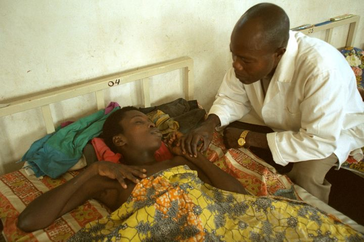 A nurse takes the pulse of a patient with sleeping sickness. The disease leads to physical and behavioral problems, seiz