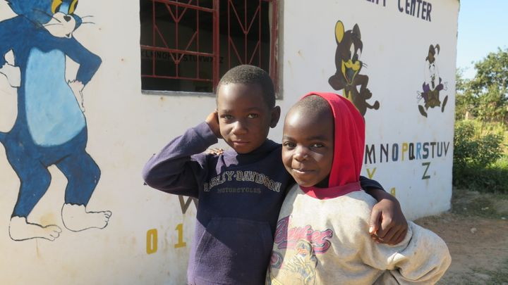 <p>Young boys in front of an ECD Center</p>