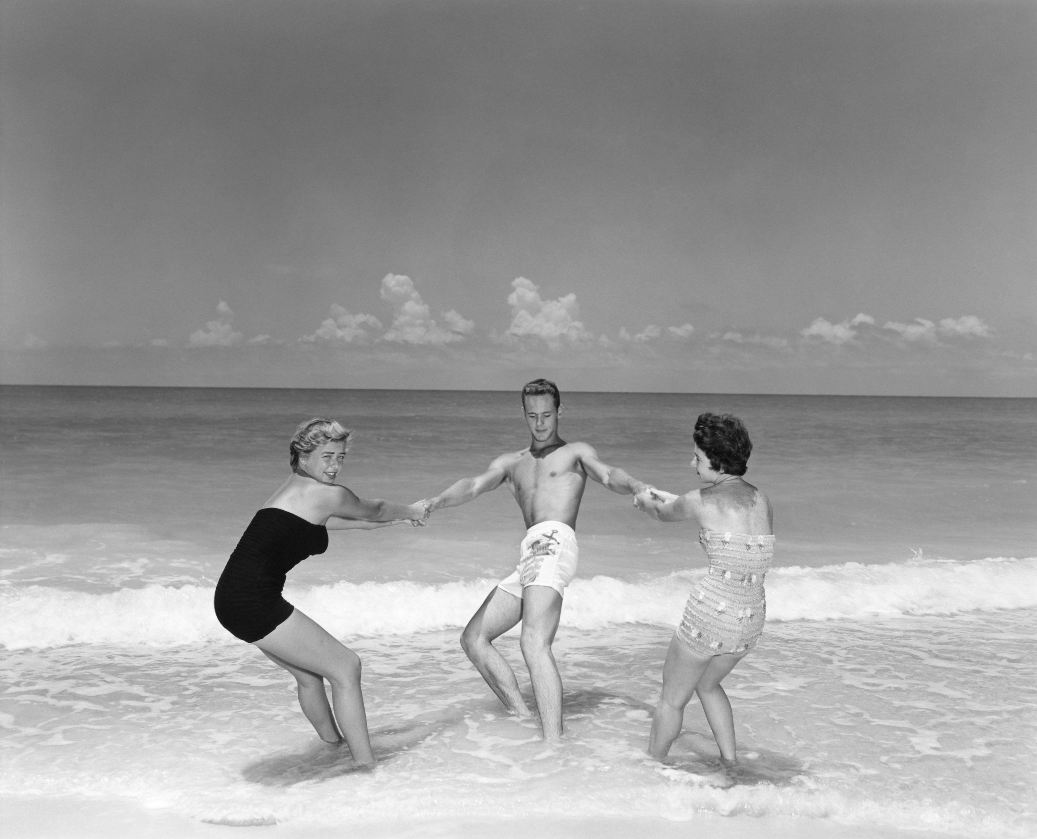 1950s MAN AND TWO WOMEN FROLICKING IN BEACH SURF  (Photo by Camerique/ClassicStock/Getty Images)