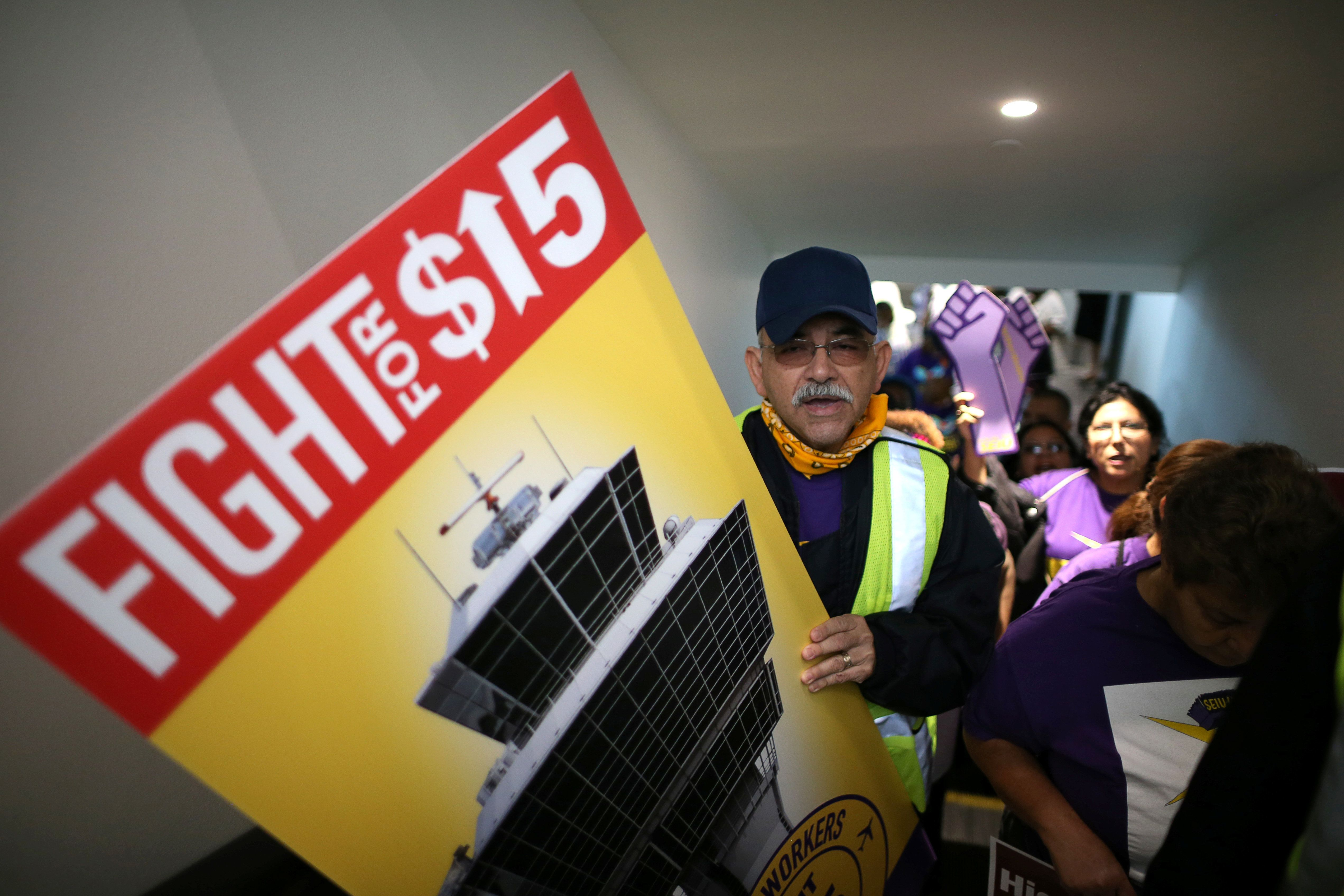 "People ride a terminal escalator in a ""Fight for $15"" wage protest at LAX airport in Los Angeles, California, U.S. November 29, 2016. REUTERS/Lucy Nicholson"