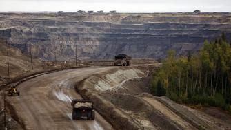 Giant dump trucks haul raw tar sands at the Suncor tar sands mining operations near Fort McMurray, Alberta, September 17, 2014. In 1967 Suncor helped pioneer the commercial development of Canada's oil sands, one of the largest petroleum resource basins in the world. Picture taken September 17, 2014.  REUTERS/Todd Korol (CANADA  - Tags: ENERGY ENVIRONMENT)