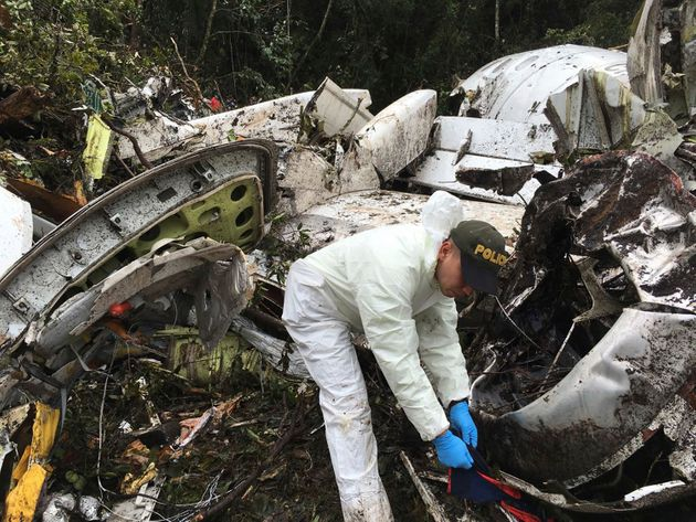 Police officers investigate the wreckage of the