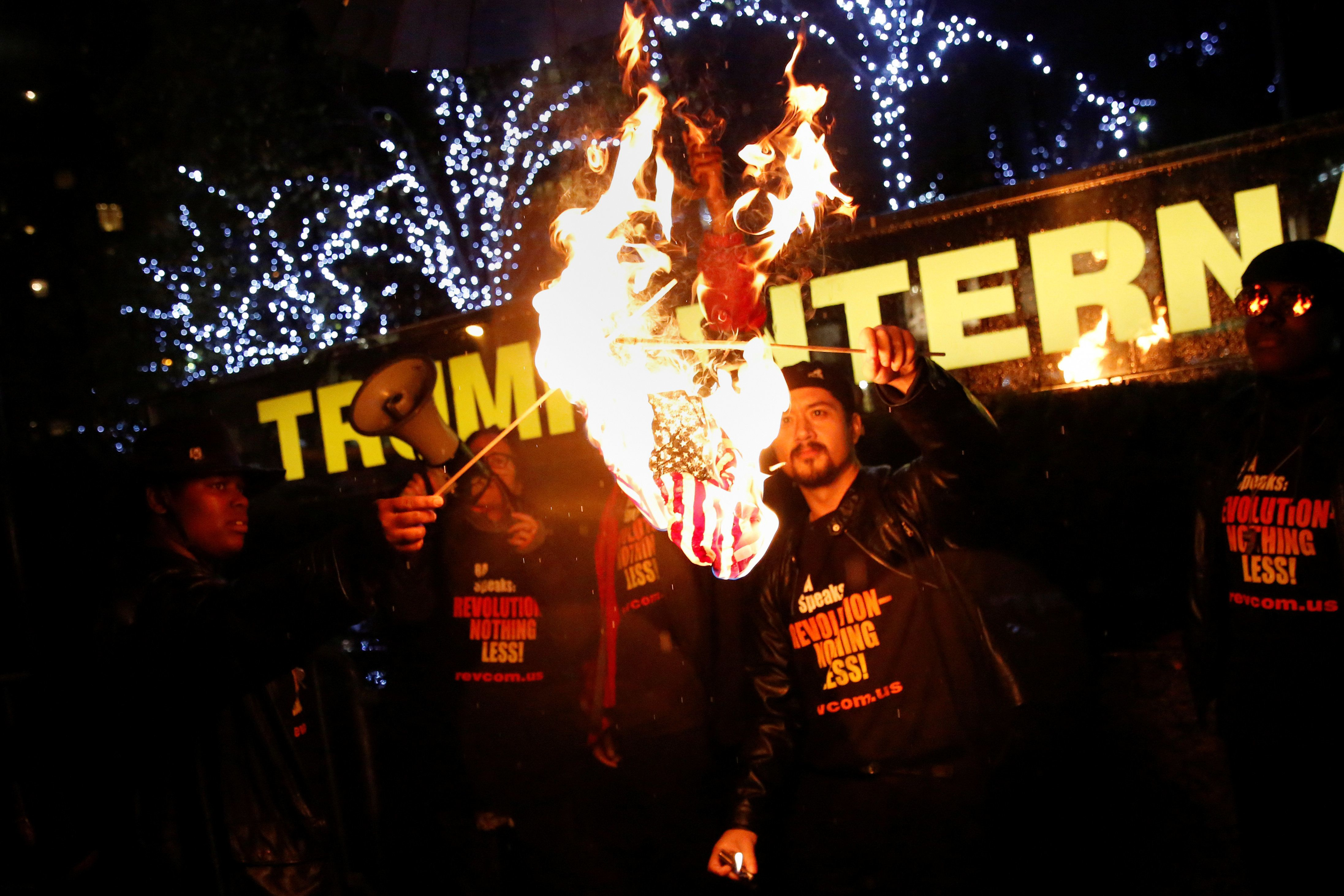 """Supporters of the """"NYC Revolution Club"""" burn the U.S. flag outside the Trump International Hotel and Tower in New York, U.S., November 29, 2016. REUTERS/Shannon Stapleton"""