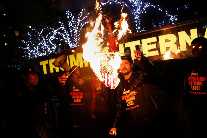 Supporters of the NYC Revolution Club burn the U.S. flag outside the Trump International Hotel and Tower in New York, U.S.