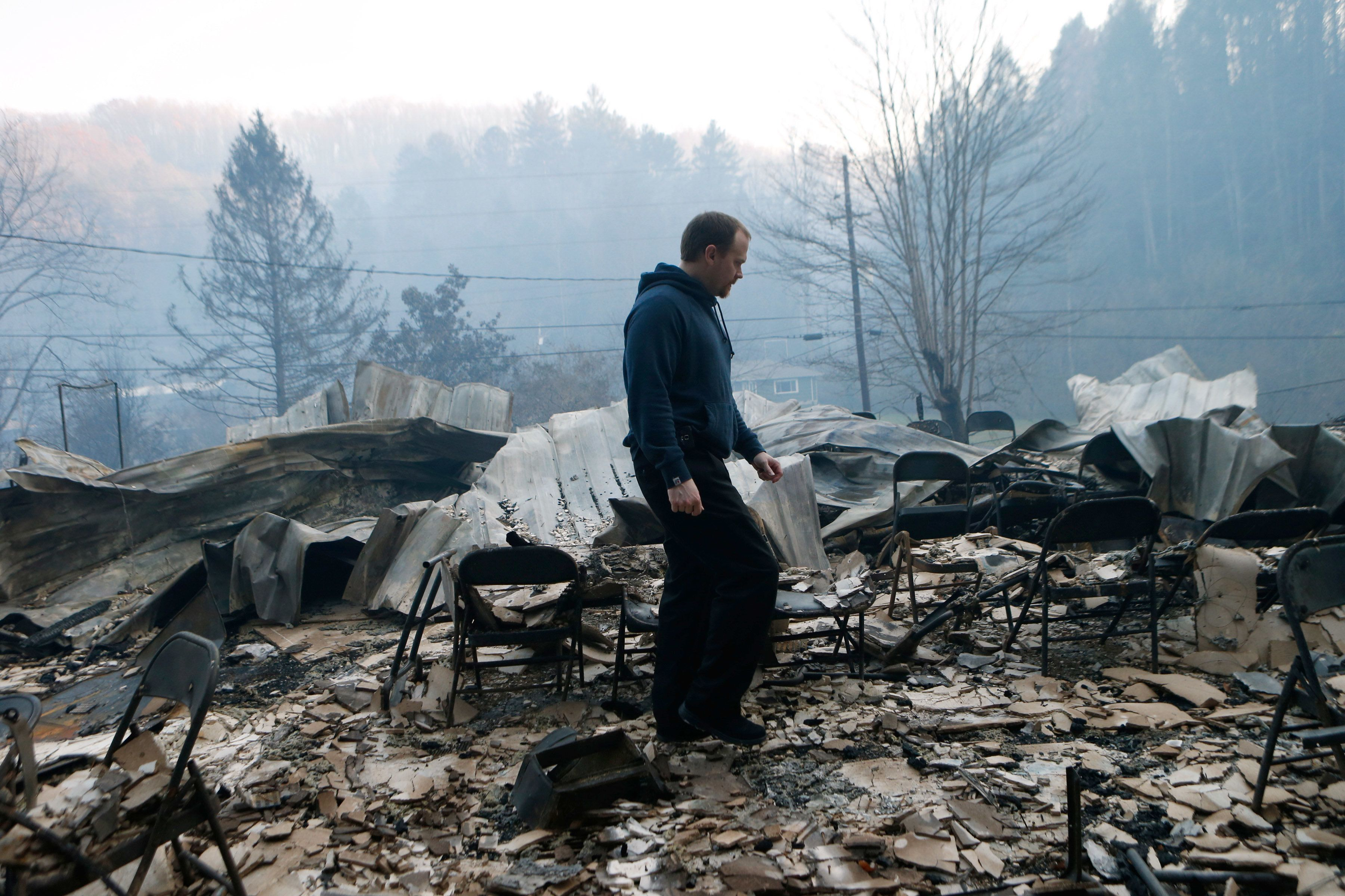 Trevor Cates walks through the smoldering remains of the Banner Missionary Baptist Church in Gatlinburg, Tennessee, after a w