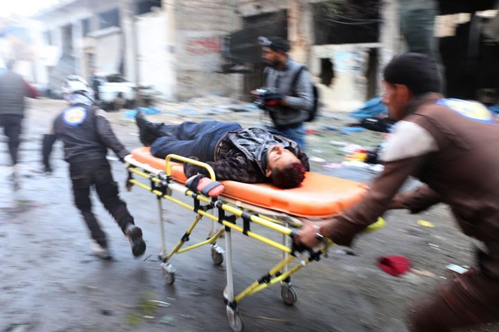 Search and rescue team members hospitalize a wounded civilian at the site of blast after Assad Regime's strike over civilians