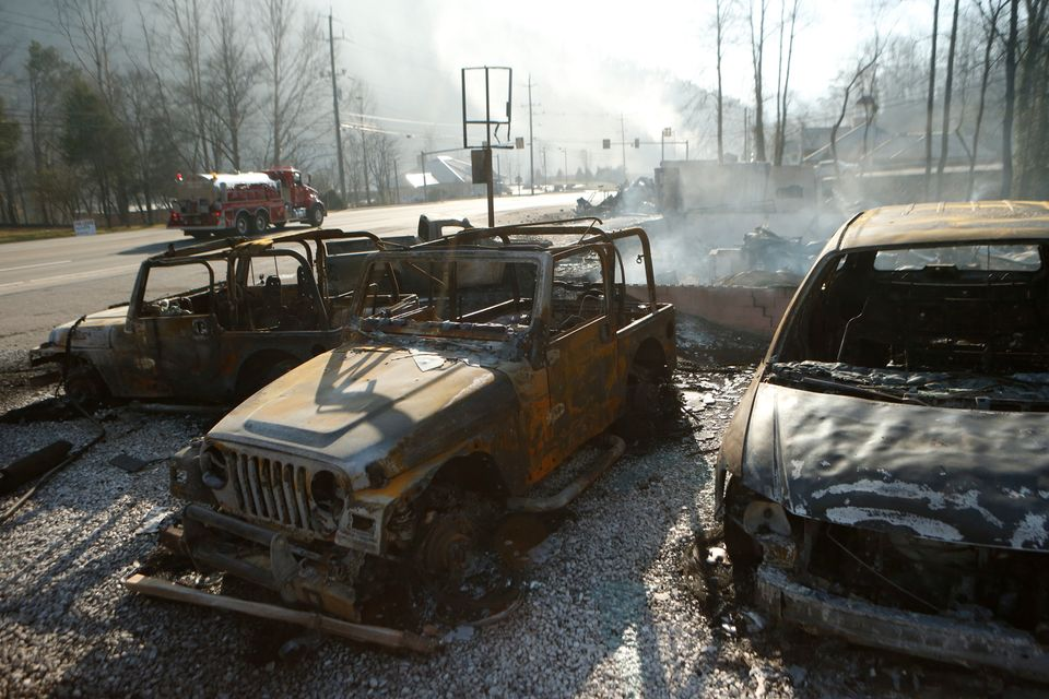 The remains of a Jeep rental business smolders after a wildfire November 29, 2016 in Gatlinburg, Tennessee. Thousands of peop