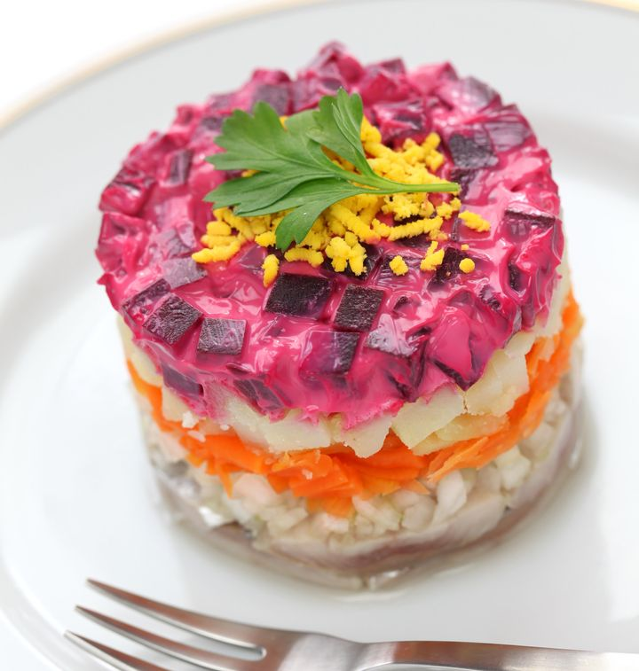 Fur-coat herring, a traditional dish layered with salted herring, cooked vegetables, and a coat of grated beets and mayo.